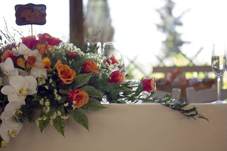 Close up of a floral bouquet as a centrepiece on a table, with glasses