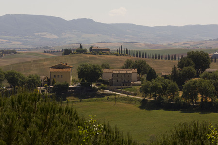 val: VAL DORCIA, ITALY - JUNE 3 2017: Hills surrounding Val Dorcia area in Tuscany region of Italy, with houses and cypress in the background Stock Photo