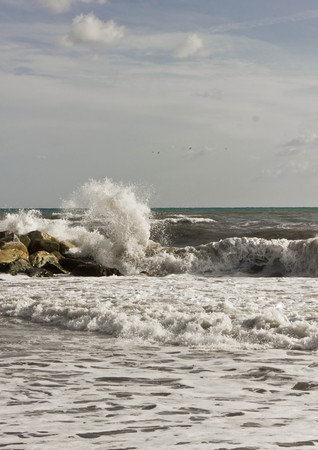 MARINA DI MASSA, ITALY - AUGUST 17 2015: Wave smash into the rocks in a sunny day with rough seas in Tuscany Redakční
