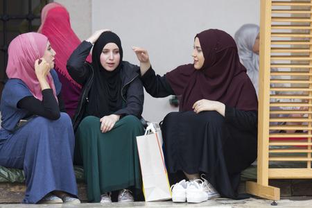 SARAJEVO, BOSNIA EN HERZEGOVINA - AUGUSTUS 20 2017: drie islamitische meisjes zitten in de binnenplaats van Gazi husrev smeden moskee in Sarajevo