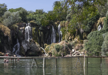 STUDENCI, BOSNIA AND HERZEGOVINA - AUGUST 16 2017: Kravice waterfalls  in Bosnia Herzegovina, with a floating wooden bridge Editorial