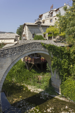 MOSTAR, BOSNIA AND HERZEGOVINA - AUGUST17 2017: Kriva Cuprija ancient bridge in Mostar, surrounded by city old buildings