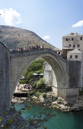 MOSTAR, BOSNIA AND HERZEGOVINA - AUGUST 17 2017: View of old Mostar bridge full of people in summer season