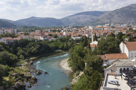 MOSTAR, BOSNIA AND HERZEGOVINA - AUGUST 17 2017: Overview of Mostar city, surrounded by mountains, and Neretva river crossing it