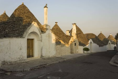 ALBEROBELLO, ITALY - AUGUST 28 2017: sunset view of a street in Alberobello, Italy