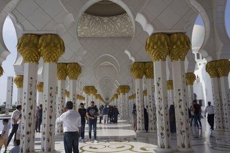 ABU DHABI, UAE - DECEMBER 28 2017: Mosque colonnade with people Redakční