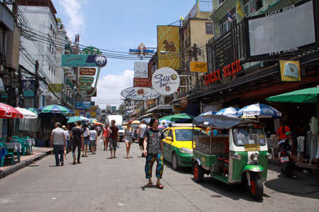 typical messy street in Bangkok downtown with many hotels, bars, taxi and tuc-tuc photo