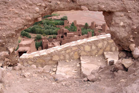 ancient atlantis: Ait ben Haddou kasbha in Morocco trough a hole in the wall Stock Photo