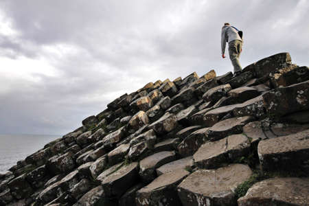 woman climbing Giants Causeway cliffs Archivio Fotografico