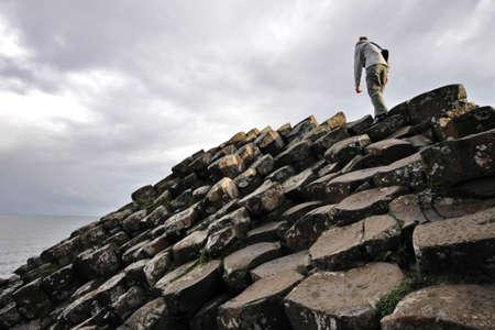 woman climbing Giants Causeway cliffs Standard-Bild