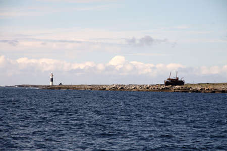 blu: view of Inisheer island with lightouse and old abandoned ship, Aran islands