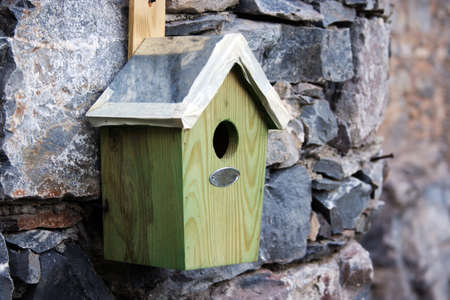little bird s house hang on a stone wall photo
