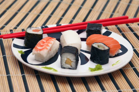 sushi plate with red chopsticks on bamboo tablecloth Stock Photo