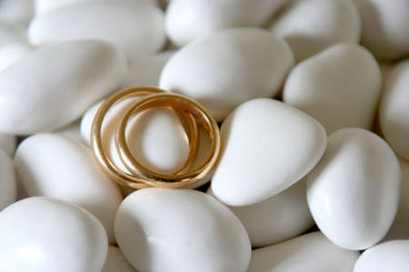 comfits: couple of golden wedding rings on white comfits still-life