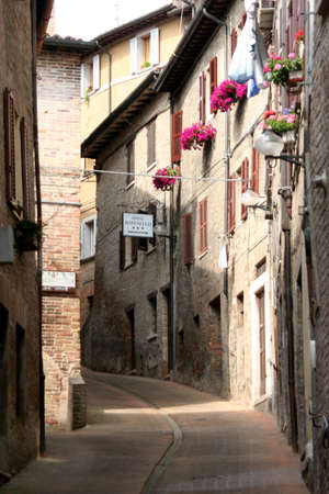 reb: typical lane with reb bricks downtown historical houses in Urbino, Italy