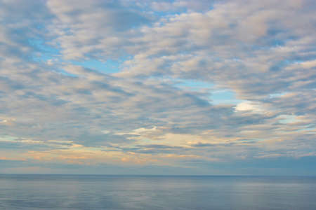 infinite light blue sky with clouds, over the sea, in italy