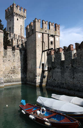 Sirmione Castle with its moat and boats, Garda Lake, Italy Imagens - 104402469