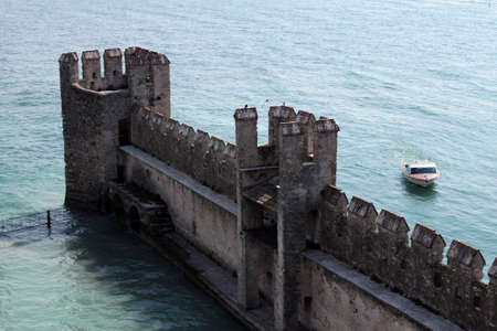 external wall of Sirmione Castle in Garda lake with a boat near it, Sirmione, nothern Italy Imagens - 104682750