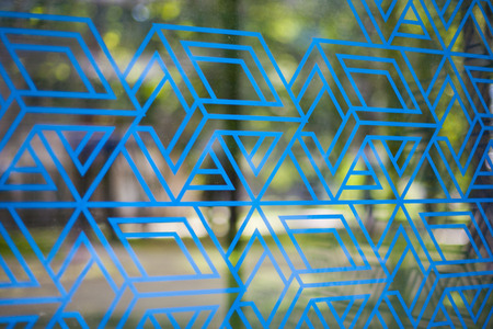 Blue angular lines and shapes on transparent glass with a blurry background