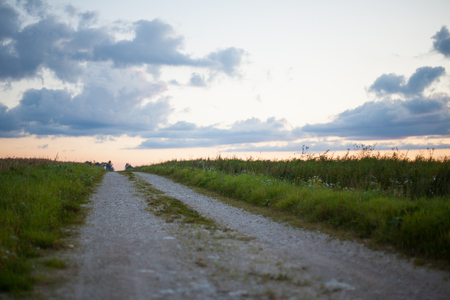 Countryside gravel road heading to the horizon at sunset Banco de Imagens
