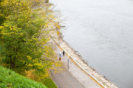 Couple of people strolling on a seaside walkway in an autumnal park