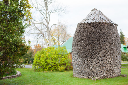 Big, cylindrical and round woodpile artwork (Holzhaufen) in a garden