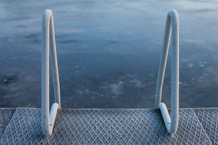 Abstract cold winter background of a frozen blue lake covered with ice and frosty swimming pool ladder, railings (winter swimming)