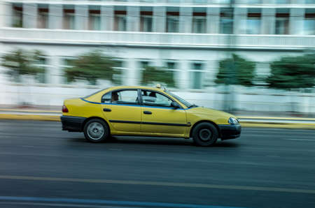 Yellow Taxi in Panning Motion in the streets of Athens Stock Photo