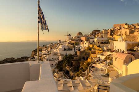 Windmills of Oia Village at Sunset, Santorini, Greece with Greek waving flag Archivio Fotografico