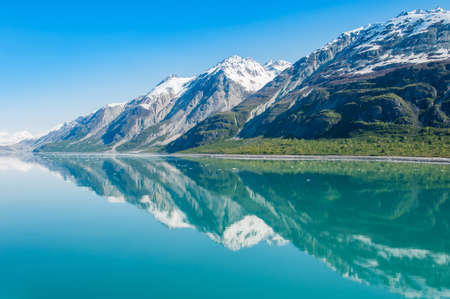 cruise travel: Mountains reflecting in still water of Glacier Bay. Glacier Bay National Park and Preserve, Alaska, United States
