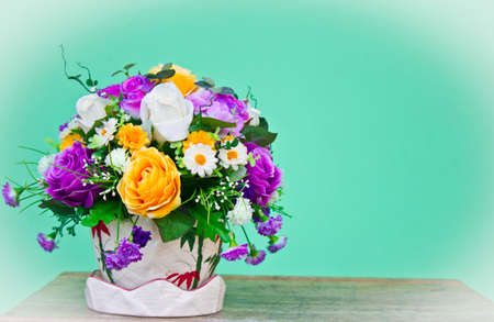Artificial flowers on green background photo