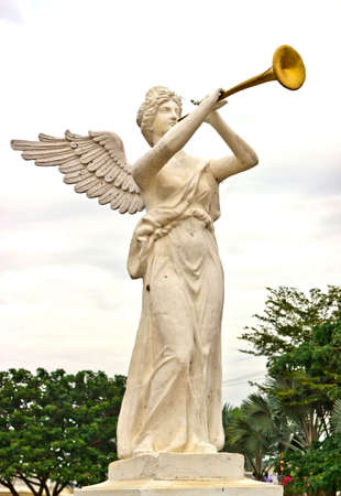 angel cemetery: A trumpeting golden music angel statue Stock Photo