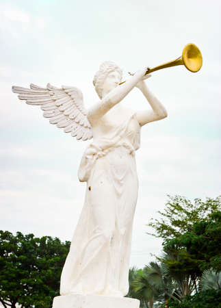 sculpture of angel blowing golden horn photo