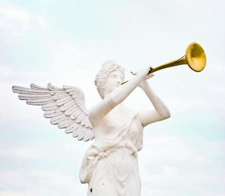 sculpture of angel blowing golden horn photo