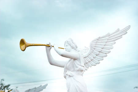 A trumpeting golden music angel statue detail photo