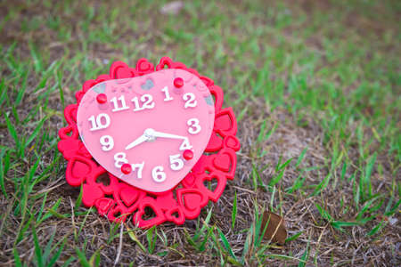 Heart-shaped clock on the grass photo