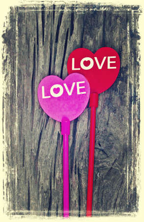 Old photo style, 2 heart and word \LOVE\ on a old wooden background photo