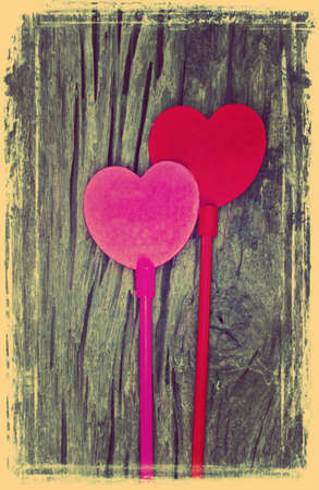 Pink and red hearts on wooden background. (Old photo style) photo