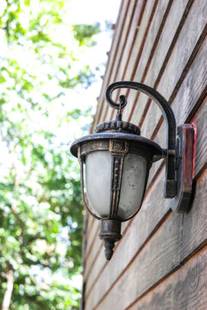 Classic lamp hanging on old wooden wall. photo