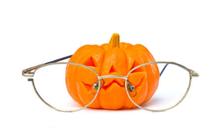 imp: pumpkin halloween day with old glasses on white background. Stock Photo