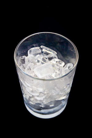 Empty glass with ice cubes on black background. Imagens