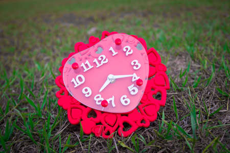 Heart shaped clock on grass. Valentines day background.
