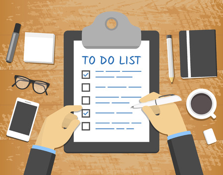 list: Flat To Do List concept - hands over clipboard on top of wooden desk