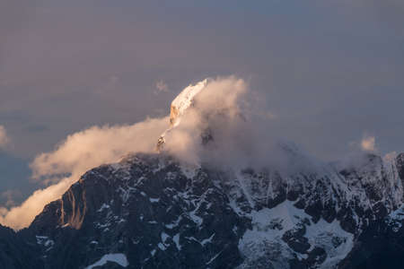 One of the holy mountains in Tibet,covered with snow,with floating clouds around in sunset light. Stock fotó