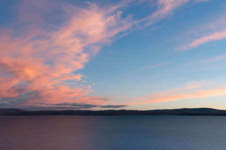 A view from high mountain located beside the Namtso Lake,morning sunlight turns clouds into beautiful pink and colorful,let them outstanding in the clear blue sky.