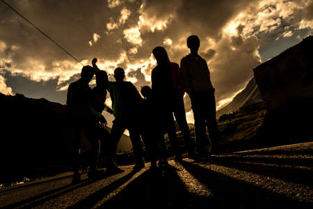 Five men with three children stand on the road with back lighting from sunset under a cloudy epic sky. Stock fotó