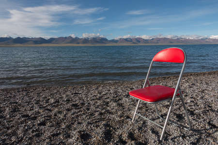 A view of a red chair placed on the beach of the Namtso Lake,with blue sky and mountains on the other side of the lake in the morning in Tibet,China.