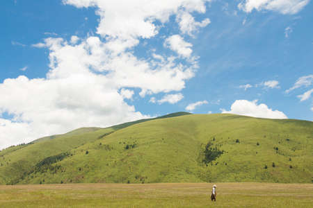 A tibetan walking in ocean of flowers called Longdeng Grassland,in front of a mountain covered with green grass and trees,under a blue sky full of white clouds in the noon.