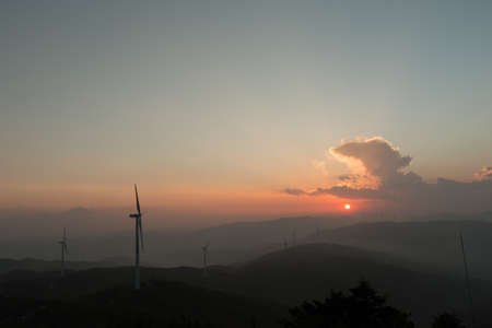 The sunset below clouds and above mountains with many wind-mill generators on them. Stock fotó