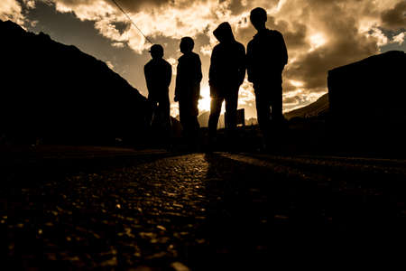 Four people stand on the road during the sunset time. Stock fotó